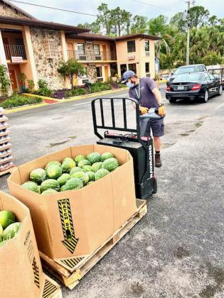 A Second Harvest Food Bank truck driver unloads a box of watermelons. NEWS-GAZETTE PHOTO/BRIAN MCBRIDE