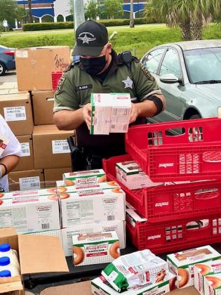 The Osceola County Sheriff's Office helped unpack some of the food. NEWS-GAZETTE PHOTO/BRIAN MCBRIDE