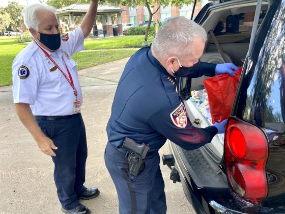 Kissimmee Police Chief Jeff O'Dell puts a bag of food in the back of a vehicle. NEWS-GAZETTE PHOTO/BRIAN MCBRIDE