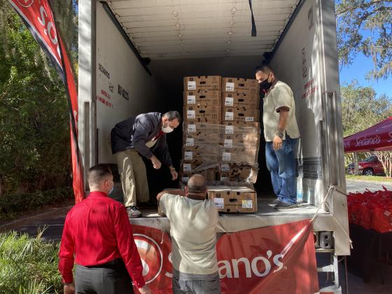 Sedano's staff members unload a pallet of food from a truck. NEWS-GAZETTE PHOTO/BRIAN MCBRIDE