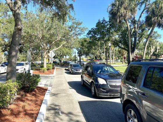 A line of cars wait for the food behind Kissimmee City Hall. NEWS-GAZETTE PHOTO/BRIAN MCBRIDE