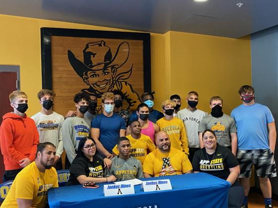 Surrounded by his parents, family and teammates, Jaekus Hines signs his letter-of-intent to wrestle for Appalachian State University. Photo courtesy of Osceola High School.