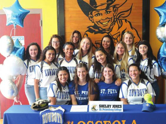 Surrounded by her teammates, Shelby Jones (front row third from right) signs her letter of intent to play softball at St. Petersburg College. PHOTO/AMANDA WATFORD
