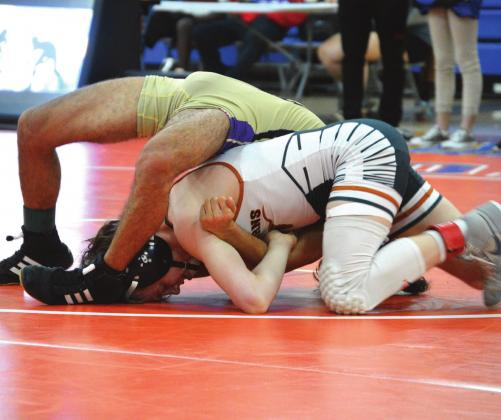 Harmony's Aiden Poe (bottom) puts the finishing touches on an opponent, one of three pins he recorded in winning the 113-pound district championship. PHOTO COURTESY OF ANDIE HINMAN/HARMONY WRESTLING