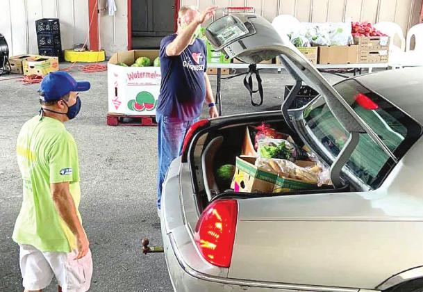 Two of the St. Cloud Community Food Pantry's 250 volunteers fills a client's trunk with food during a recent drive through distribution. The organization was one of several local pantries to receive financial assistance from disaster relief organization. SUBMITTED PHOTO